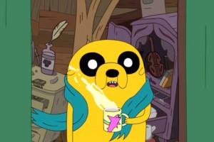 Foto de Jake el Perro de la caricatura Hora de Aventura, sosteniendo una taza de cafe mientras el fresco de la mañana pega en su cara. Por suerte tiene una bufandita azul.