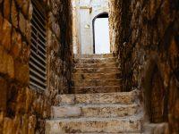Una escalinata en un pasillo angosto que conduce a una puerta abierta donde se observa el cielo