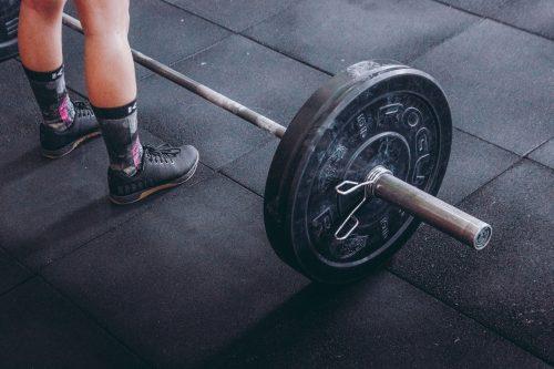 Foto de una persona de pie frente a una barra con pesas