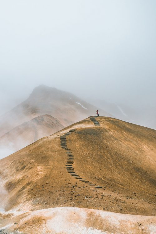Foto de un hombre en la cima de un cerro con un sendero. Detrás se ve otro cerro más alto, entre la neblina.