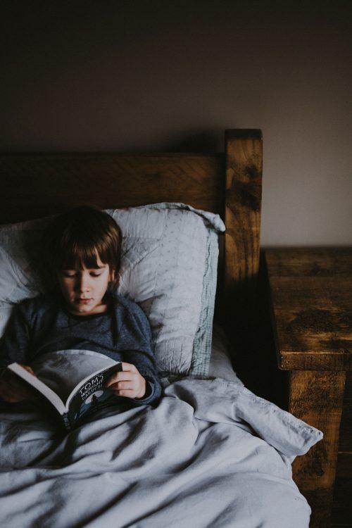 Foto de un niño en la cama leyendo un libro.