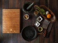 Foto de una mesa con ingredientes listos para cocinar y una tabla de cocina.