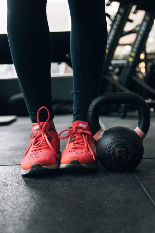 Foto de los pies de una mujer en zapatillas junto a una pesa en un gimnasio.