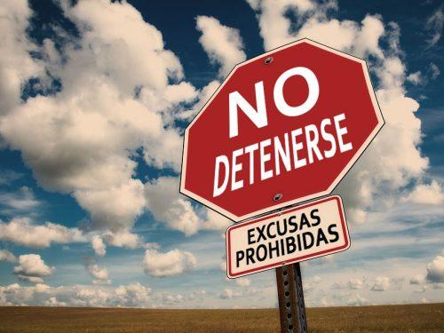 """Foto de un cartel vial que en lugar de decir """"STOP"""" dice """"No detenerse"""" y debajo """"Excusas prohibidas."""" De fondo una llanura y un cielo soleado con algunas nubes"""