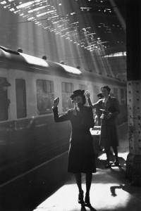 Una foto en blanco y negro de una mujer despidiendose en el anden de un tren