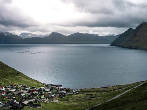 Foto de un pequeño pueblo a la orilla de un lago situado en un valle entre montañas