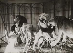 Foto en blanco y negro de una mujer domando leones