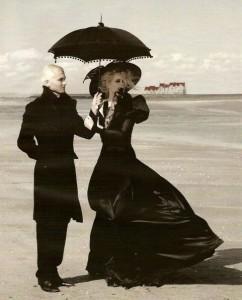 Foto de un hombre sosteniendo una sombrilla para una mujer en una playa