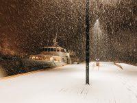 Foto de un barco anclado a un muelle iluminado en la noche, mientras cae una tormenta de nieve