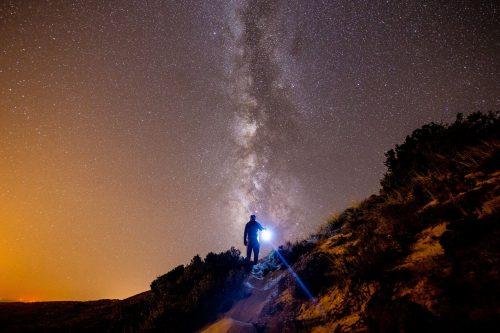 Foto de un joven sosteniendo un farol en un camino ; a su izquierda el amanecer y a su derecha la noche estrellada.