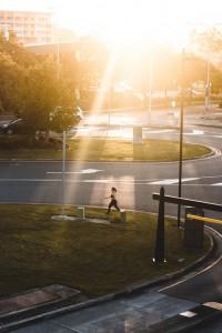 Mujer trotando en una calle soleada con pasto