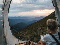 Una niña mirando un paisaje de montaña desde adentro de una carpa con luces