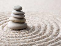 Cinco piedras apiladas sobre arena con círculos concéntricos