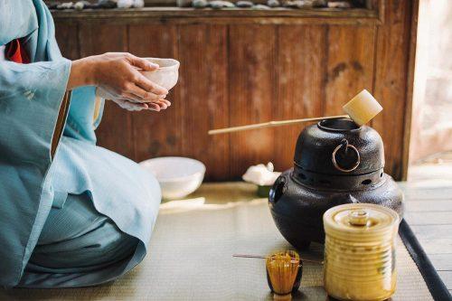 Foto de una japonesa sentada con un cuenco de té, realizando la ceremonia