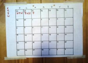 Una foto de un calendario dibujado a mano pegado a una pared de madera