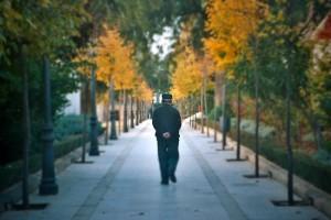 Un hombre mayor dando un paseo en una calle peatonal con árboles a los costados