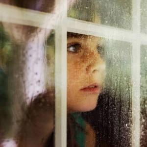 Foto de una niña mirando por una ventana lluviosa