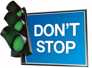 """Semáforo con las tres luces en verde, junto a un cartel que dice """"Don't Stop"""" (""""No te detengas"""" en inglés)"""