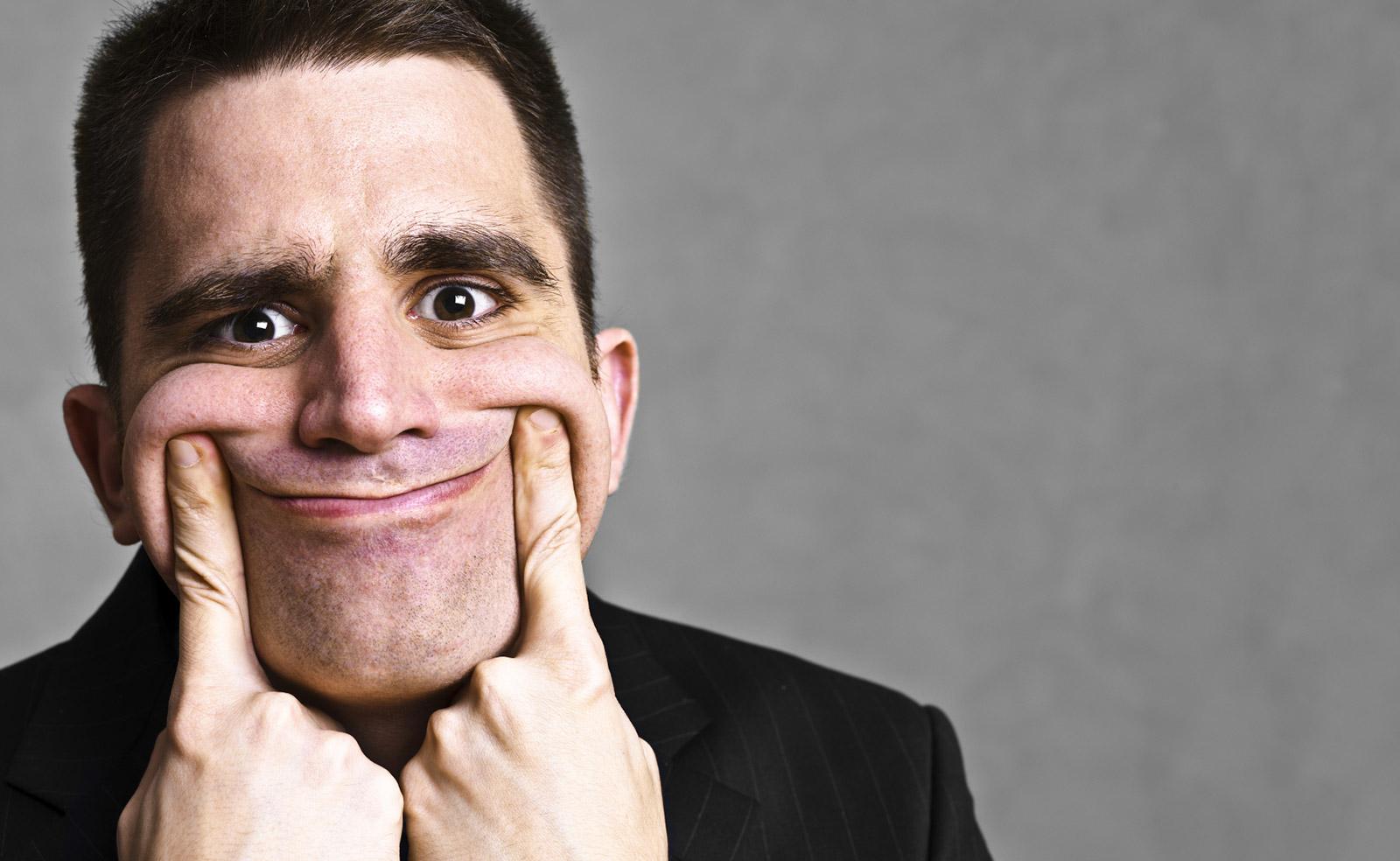 Hombre forzando una sonrisa con sus dedos
